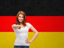 Vrouw die in t-shirt op u over Duitse vlag richten Stock Foto's