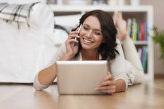 Vrouw die tablet en telefoon met behulp van Stock Afbeeldingen