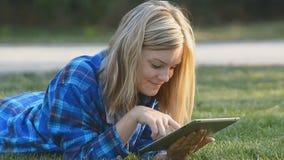 Vrouw die tablet het openlucht leggen op gras gebruiken stock footage