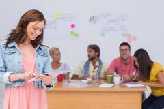 Vrouw die tablet met creatief team gebruiken die achter haar werken Stock Afbeeldingen