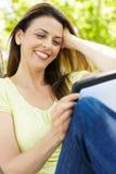 Vrouw die tablet in openlucht gebruikt Royalty-vrije Stock Afbeeldingen