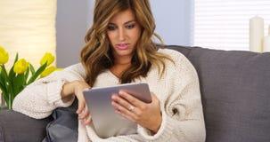 Vrouw die tablet in woonkamer gebruikt stock foto's