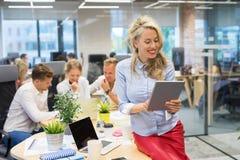 Vrouw die tabletcomputer in bureau met behulp van stock foto