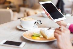 Vrouw die tabletcomputer in koffie met behulp van Royalty-vrije Stock Afbeeldingen