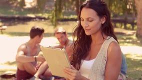Vrouw die tabletcomputer met haar vrienden achter haar in park met behulp van stock videobeelden