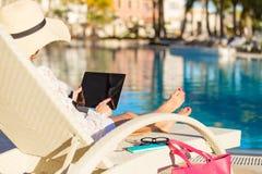 Vrouw die tabletcomputer op vakantie in luxetoevlucht met behulp van Stock Foto's