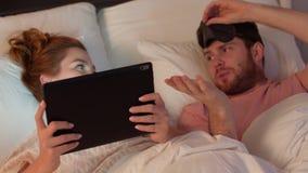 Vrouw die tabletpc en het gestoorde man awaking gebruiken stock videobeelden