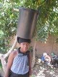 Vrouw die tactvol een emmer water op haar hoofd in evenwicht brengen Stock Afbeeldingen