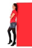 Vrouw die tegen aanplakbord leunt Stock Foto's