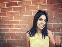 Vrouw die tegen bakstenen muurachtergrond glimlachen stock afbeeldingen