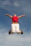 Vrouw die tegen blauwe hemel springt royalty-vrije stock foto