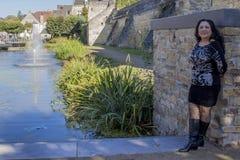 Vrouw die tegen een steenmuur leunen met een beek en fonteinachtergrond royalty-vrije stock foto