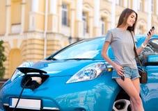 Vrouw die telefoon dichtbij hybride auto bekijken stock afbeeldingen