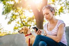 Vrouw die telefoon in het park met behulp van royalty-vrije stock foto's