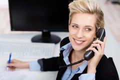 Vrouw die Telefoon met behulp van terwijl het Kijken omhoog in Bureau Stock Foto's