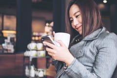Vrouw die telefoon met hete koffie met behulp van stock afbeelding