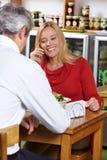 Vrouw die telefoon in restaurant met behulp van Royalty-vrije Stock Foto's