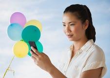 Vrouw die telefoon tegen hemel en ballons bekijken royalty-vrije stock afbeeldingen