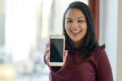 Vrouw die telefoon tonen stock afbeelding