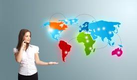 vrouw die telefoongesprek met kleurrijke wereldkaart maken stock foto