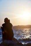 Vrouw die telefoongesprek met zonsondergang maken bij strand Stock Foto's