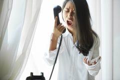 Vrouw die in telefoonontvanger schreeuwen stock fotografie