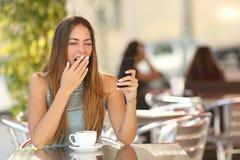 Vrouw die terwijl bij ontbijt in een restaurant werkt geeuwen Stock Afbeelding