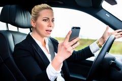 Vrouw die terwijl het drijven door auto texting Royalty-vrije Stock Foto's