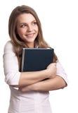 Vrouw die terwijl het houden van boek glimlacht Stock Fotografie