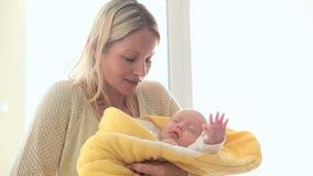 Vrouw die terwijl het houden van een kind in een gele deken glimlachen stock videobeelden