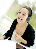 Vrouw die terwijl het luisteren aan hoofdtelefoons lachen Royalty-vrije Stock Foto
