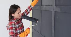 Vrouw die terwijl het schilderen van blokhuismuur met een rol genieten van stock video