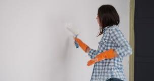 Vrouw die terwijl het schilderen van huismuur met een rol genieten van stock footage
