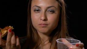 Vrouw die tevreden etend heerlijke pizza en drinkend een kolasoda kijken stock footage