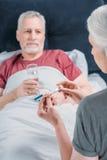 Vrouw die thermometer bekijken terwijl het behandelen van zieke echtgenoot stock afbeeldingen