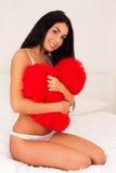 Vrouw die thuis een groot pluizig zacht hart koestert Stock Fotografie
