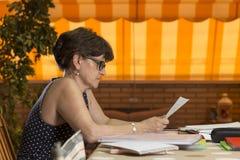 Vrouw die thuis met verscheidene omslagen en partijen van documenten werken royalty-vrije stock afbeeldingen