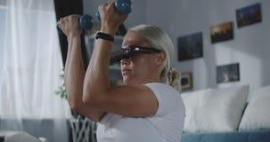 Vrouw die thuis met VR-hoofdtelefoon uitwerken stock videobeelden