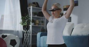 Vrouw die thuis met VR-hoofdtelefoon uitwerken stock video