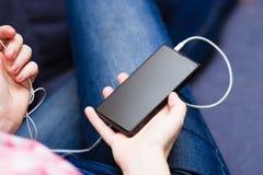 Vrouw die thuis op bank zitten die op smartphone met wifi doorbladeren Royalty-vrije Stock Foto