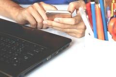 Vrouw die thuis op witte lijst en zwarte laptop, gadget i ontspannen Royalty-vrije Stock Afbeeldingen