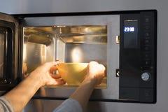 Vrouw die thuis voedsel verwarmen bij magnetron royalty-vrije stock fotografie