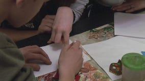 Vrouw die tienerjongen helpen door katoenen zwabber bij lijst trekken festival verwezenlijking Gemaakte hand - stock videobeelden