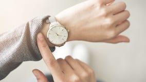 Vrouw die tijd controleren haar horloge royalty-vrije stock afbeelding