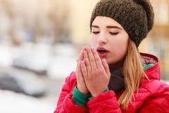 Vrouw die tijdens de winter haar handen opwarmen stock foto