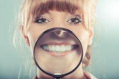 Vrouw die tonend tanden met vergrootglas glimlachen royalty-vrije stock afbeeldingen