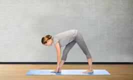 Vrouw die tot yoga maken intense rek op mat stellen Royalty-vrije Stock Afbeelding