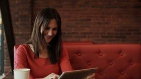 Vrouw die touchscreen en de lach van de tabletcomputer in koffie gebruiken stock videobeelden