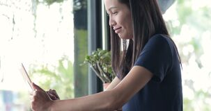 Vrouw die touchscreen van de tabletcomputer in koffie gebruiken stock video