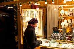 Vrouw die traditioneel Kerstmisspeelgoed kopen Royalty-vrije Stock Foto